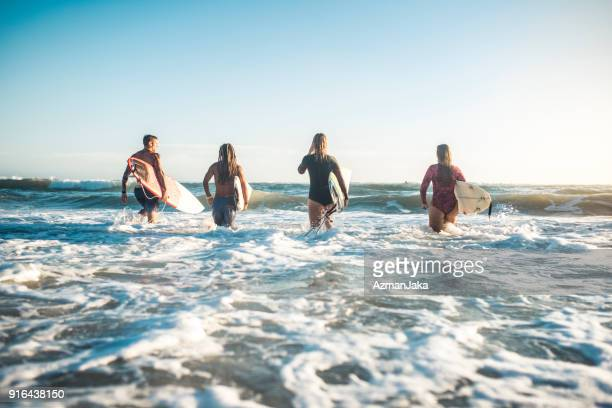 Group of people running into the ocean with surfboards