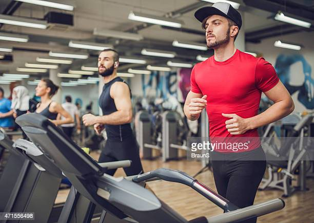 Group of people running on treadmills in a health club.