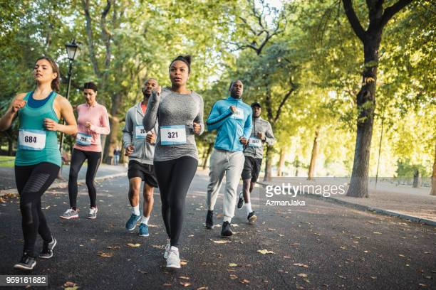 group of people running track together in a park - maratona foto e immagini stock