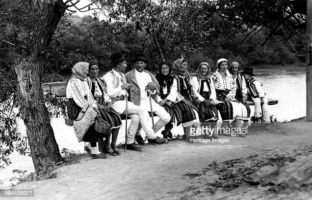 Group of people seated on a bench, Bistrita Valley, Moldavia, north-east Romania, c1920-c1945. Depicting customs and traditional labour in the rural...
