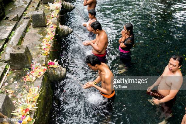 group of people showering under the waterspouts at the tirta empul temple in bali, indonesia - pura tirta empul temple stock pictures, royalty-free photos & images