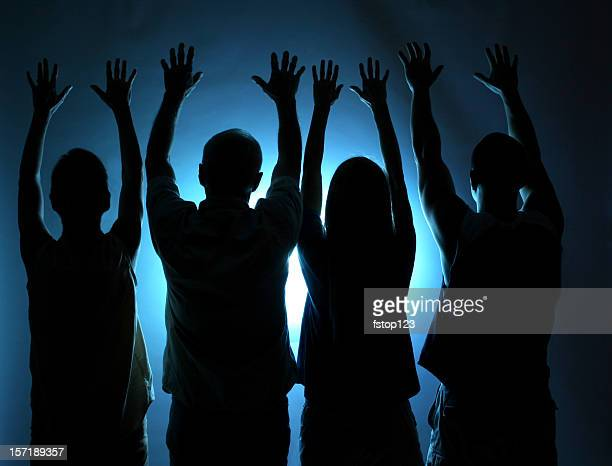 group of people silhouette. arms raised in praise. blue light. - congregation stock pictures, royalty-free photos & images