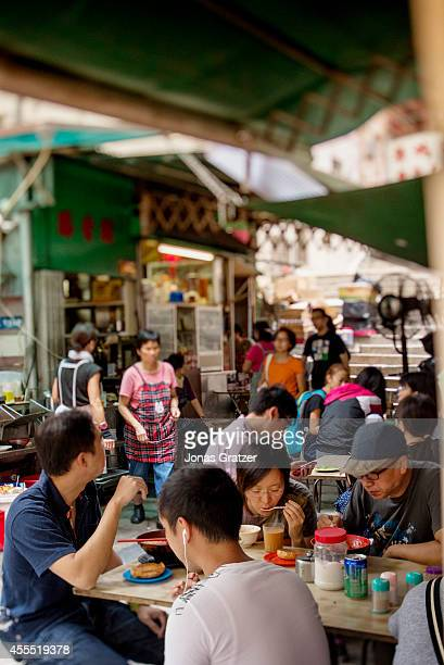 A group of people sit around tables laid out on the street for some traditional Asian street noodles and other street food delights