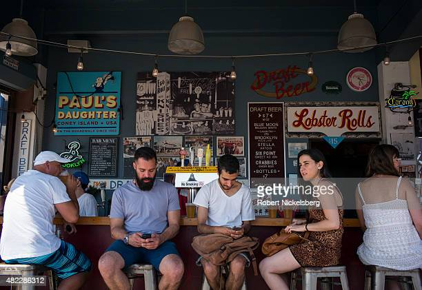 A group of people sit at a bar using their iPhones along the boardwalk July 24 2015 at Coney Island Beach in the Brooklyn borough of New York