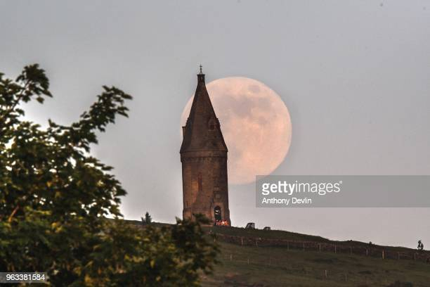 A group of people sit at the base of Hartshead Pike as the Flower Moon rises at 986% on May 28 2018 in Manchester England The tower was rebuilt in...