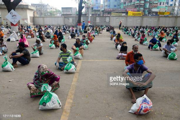Group of people sit in a queue to receive relief supplies amid Coronavirus crisis. During the Coronavirus crisis besides the government, many...