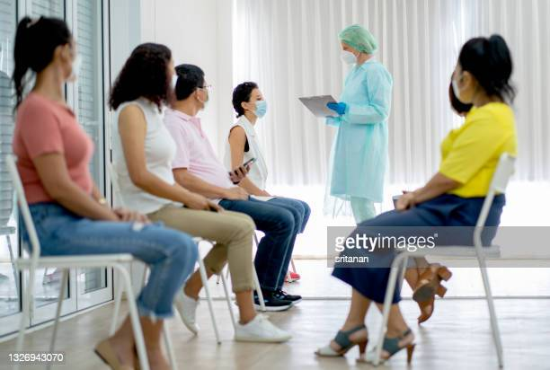 group of people sit on chair in two roles waiting for covid-19 vaccination and medical staff with green uniform hold document chart - legal trial stock pictures, royalty-free photos & images