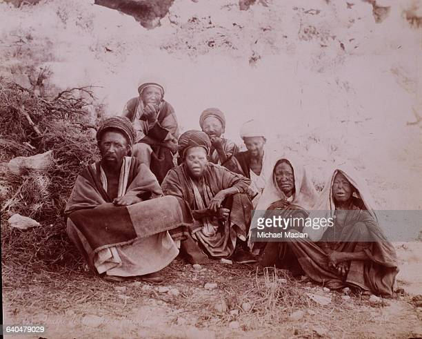 A group of people sit together exiles due to their affliction with leprosy in Jeruselem Palestine ca 1870s