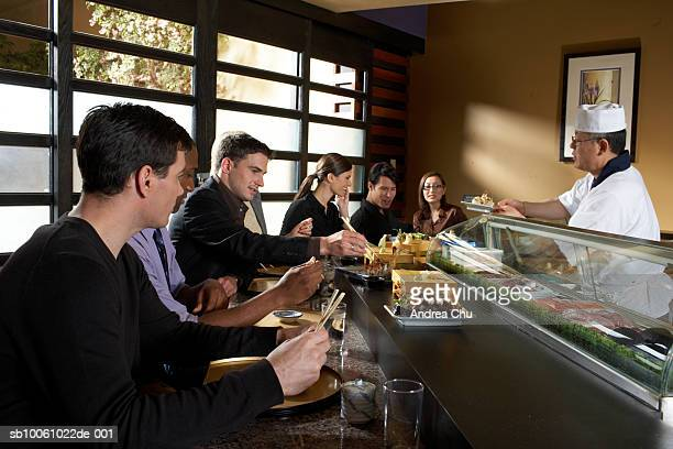 group of people sitting at counter in sushi bar, waiter serving meal - sushi restaurant stock photos and pictures