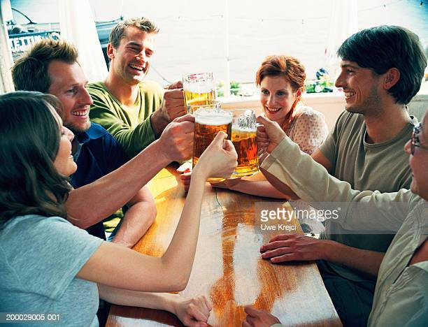 Group of people sitting at table in ship's cabin raising glasses