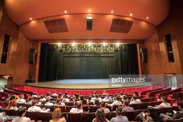 groupe de gens assis au théâtre en attente pour l'exécution de commencer - theatrical performance photos et images de collection