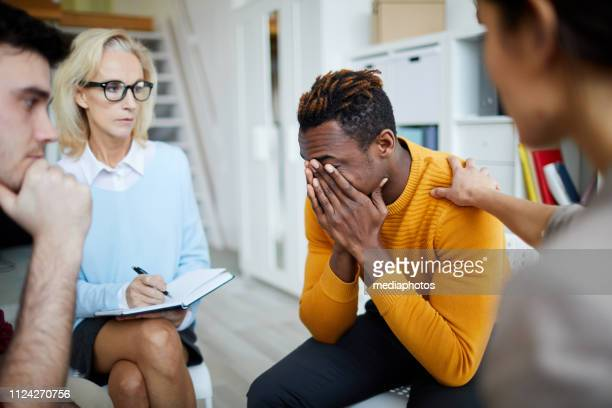 Group of people sitting in circle and sharing their problems and addictions: woman supporting crying black man and touching his shoulder at group psychotherapy session