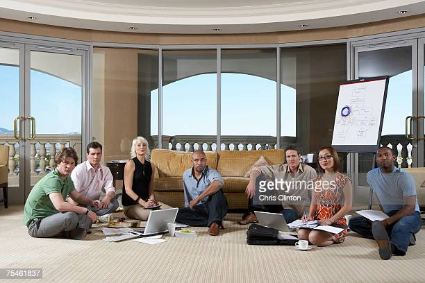 group of people sitting in hotel room with laptop, portrait - hand on knee stock pictures, royalty-free photos & images