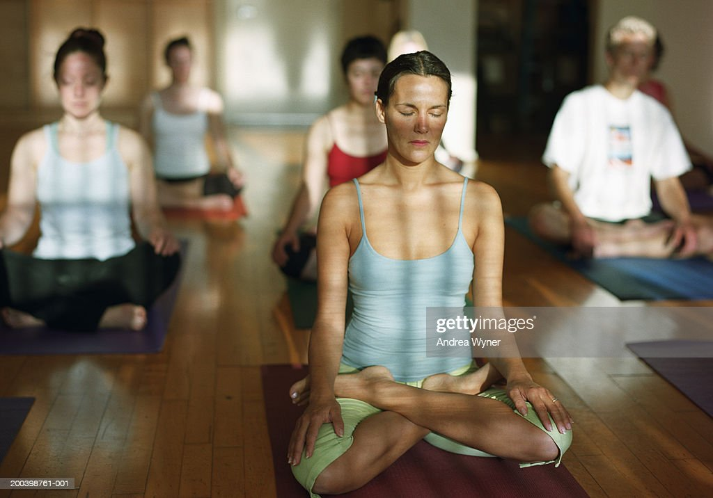 Group of people sitting in lotus position in yoga class, eyes closed : Stock Photo