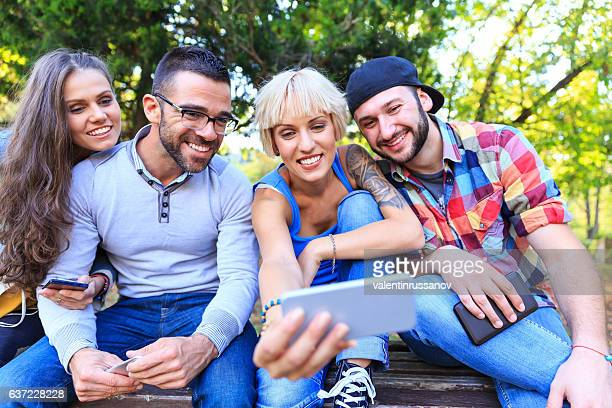 Group of people sitting in park and making selfie