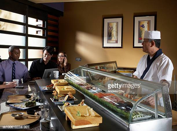 group of people sitting in sushi bar, waiter behind counter, one man using laptop - sushi restaurant stock photos and pictures
