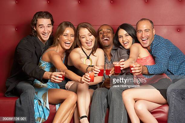 group of people sitting on a couch holding glasses - clubkleding stockfoto's en -beelden
