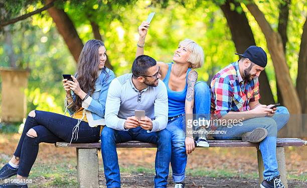 Group of people sitting on bench and using smart phone
