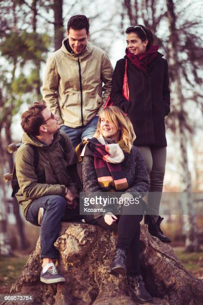 Group Of People Sitting On Big Tree Trunk