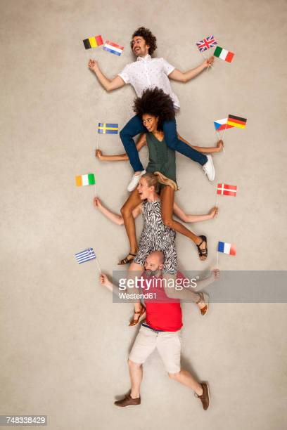 Group of people sitting on each other's shoulders, holding European flags