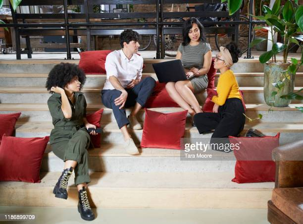 group of people sitting on stairs with laptop - employee stock pictures, royalty-free photos & images