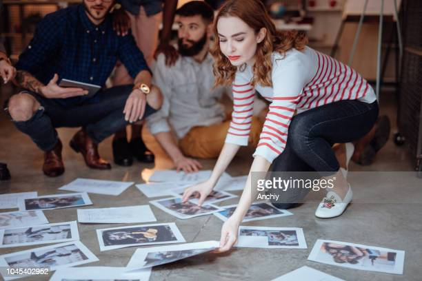 Group of people sitting on the floor and looking at photos