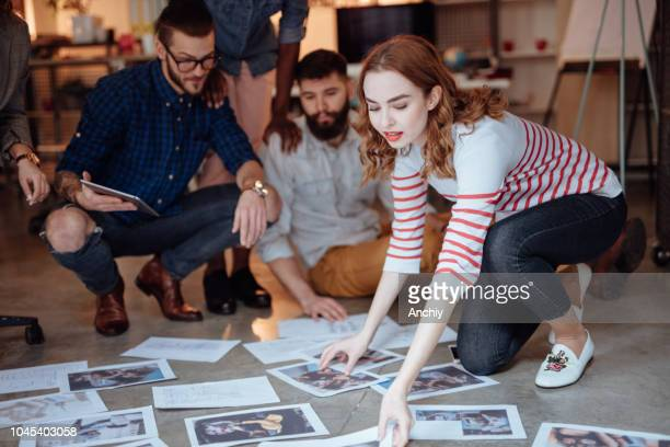 group of people sitting on the floor and looking at photos - editor stock pictures, royalty-free photos & images