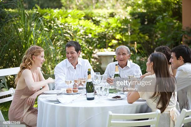 Grupo de pessoas sentado ao ar livre à Mesa a falar e sorrir