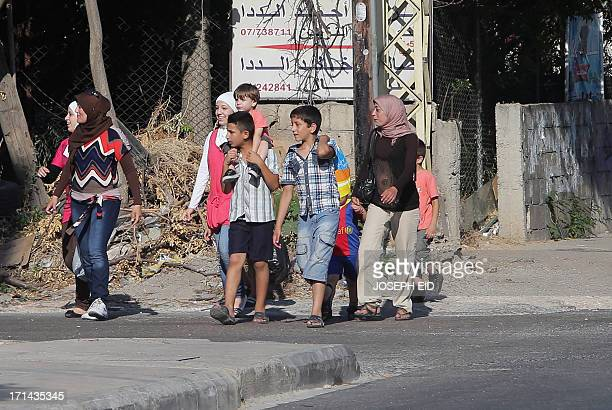 A group of people smile upon their arrival at a safe zone at the entrance of the district of Abra near the southern Lebanese city of Sidon on June 24...