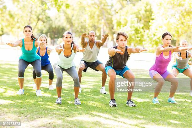 Group of People Squating In Bootcamp Class