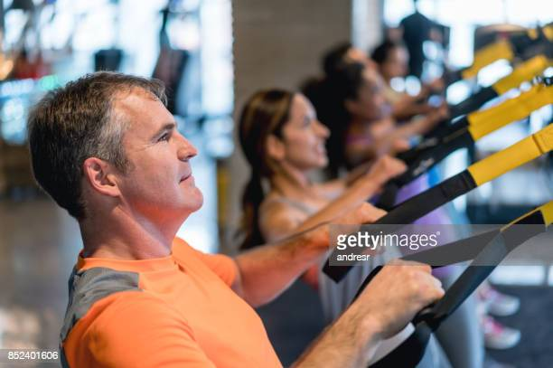 Group of people sspension training at the gym