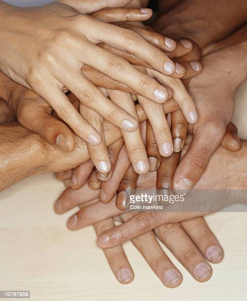 Group of people stacking hands on top of each other, close-up