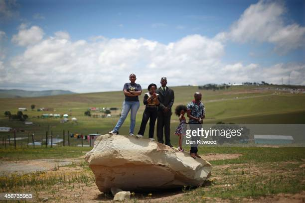 A group of people stand on a rock overlooking the funeral service of the former South African President Nelson Mandela during his state funeral on...