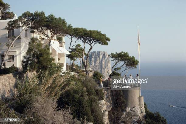 A group of people stand on a terrace at the Unghia Marina on the island of Capri Italy in September 1989 Trees dot the side of the marina while a...