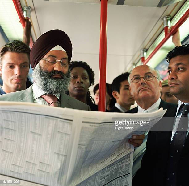 Group of People Stand on a Train Around a Man Reading a Broadsheet Newspaper