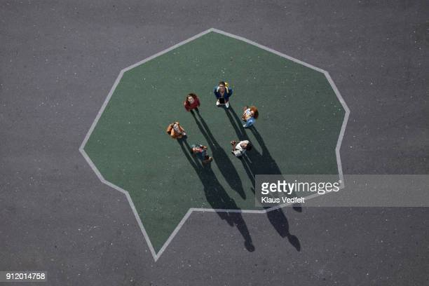Group of people standing a circle inside speech bubble, painted on asphalt and looking up