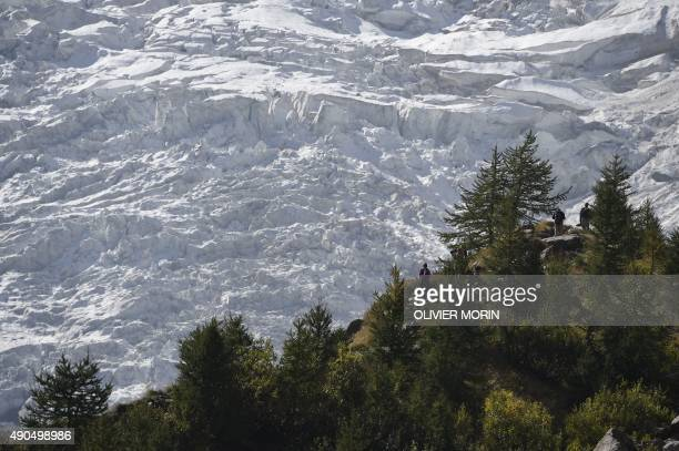Group of people standing along the Belvedere glacier look at one of the three glaciers of the Monte Rosa on September 26, 2015. The Belvedere Glacier...