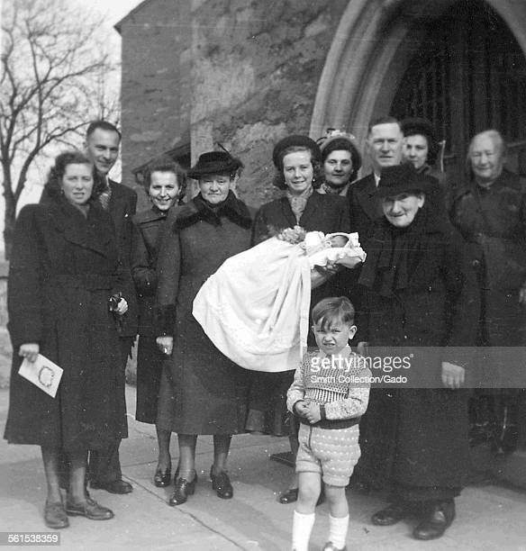 Group of people standing at the entrance of a church a woman holding a baby in the center a christening Germany January 6 1955