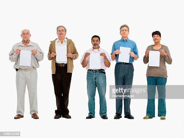 Group of people standing in a row holding papers