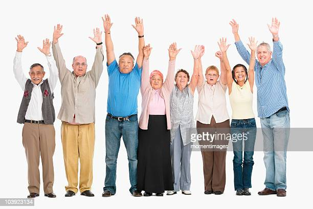 A group of people standing in a row raising their arms