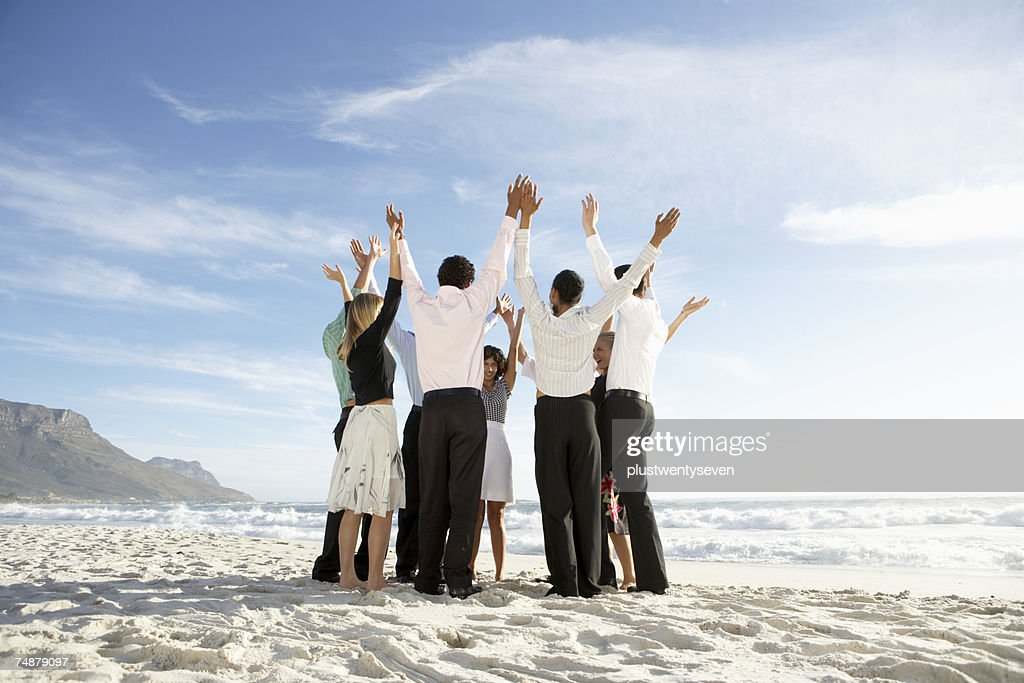 Group of people standing in circle on beach, arms raised : Stock Photo