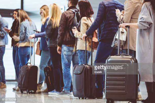 group of people standing in queue at boarding gate - tourist stock pictures, royalty-free photos & images
