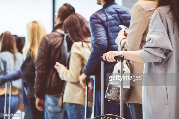 group of people standing in queue at boarding gate - lining up stock pictures, royalty-free photos & images