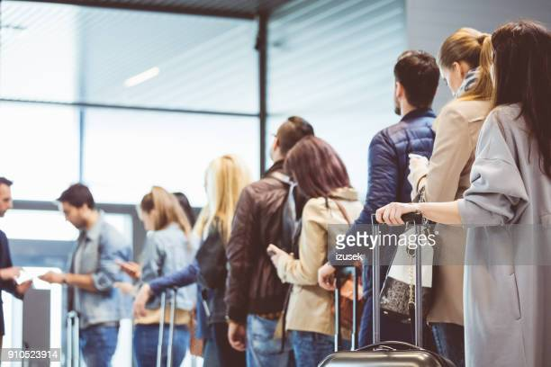 group of people standing in queue at boarding gate - affollato foto e immagini stock