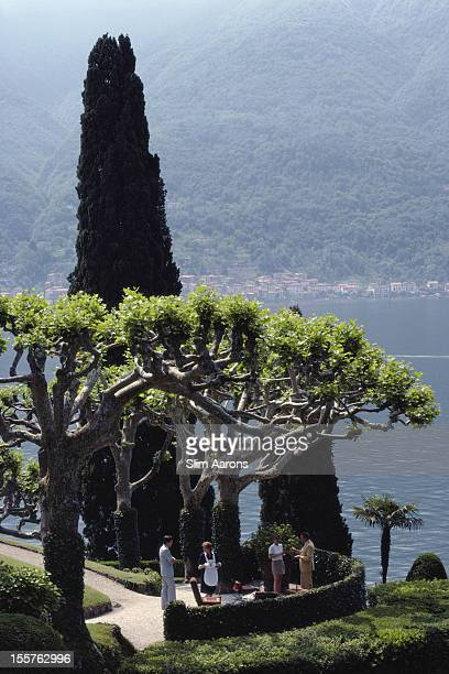 Group of people standing in the shade of a tree on a terrace in the garden at the Villa del Balbianello in Lenno, overlooking Lake Como, Italy, in...