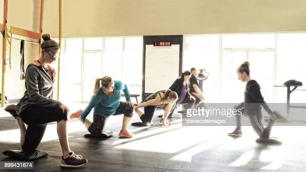 Group of people stretching in gym with instructor