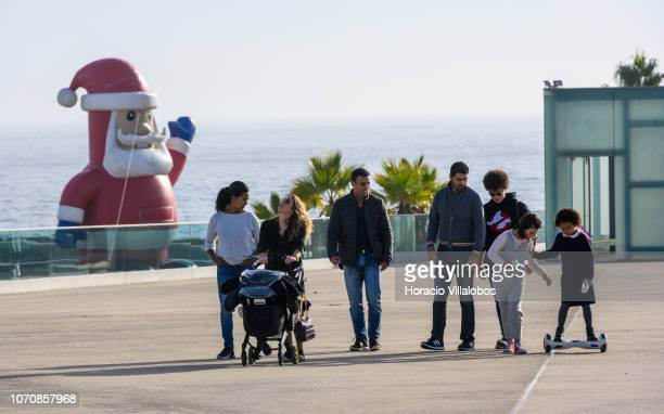 A group of people stroll past a large inflatable Santa Claus greeting those coming into the Marina de Cascais in a sunny Sunday afternoon on December...