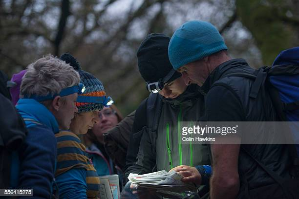 Group of people studying map with headtorches