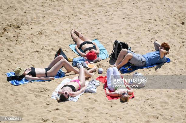 Group of people sunbathe on the beach on May 31, 2021 in Bournemouth, England.