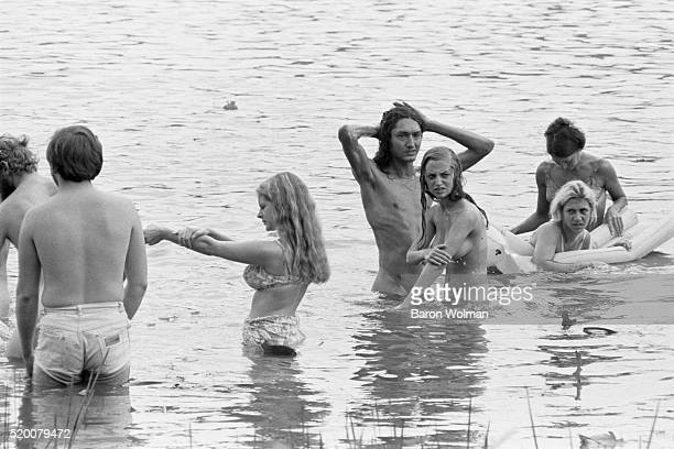 A group of people swim naked in the lake at the Woodstock Music Art Fair Bethel NY August 15 1969